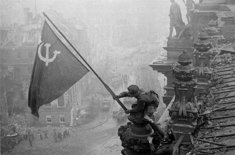 The Soviet army hoisting its flag over the German Reichstag after the battle for Berlin in 1945